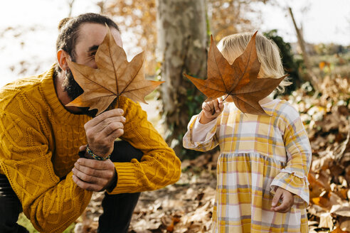 Father and daughter enjoying a morning day in the park in autumn, playing with autumn leaves - JRFF02254