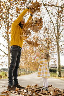 Father and daughter enjoying a morning day in the park in autumn, throwing autumn leaves - JRFF02257