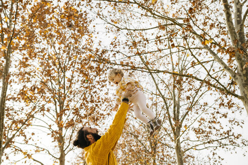 Father throwing his daughter in air, in a park in autumn - JRFF02260