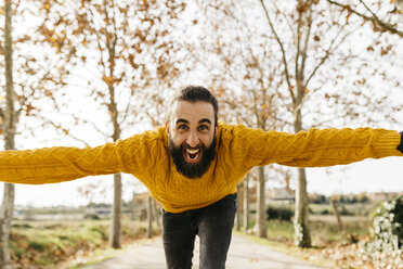 Young man with open arms and happy in a park in autumn - JRFF02263