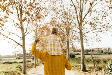 Father carrying his little daughter on shoulders in the morning, park in autumn - JRFF02266
