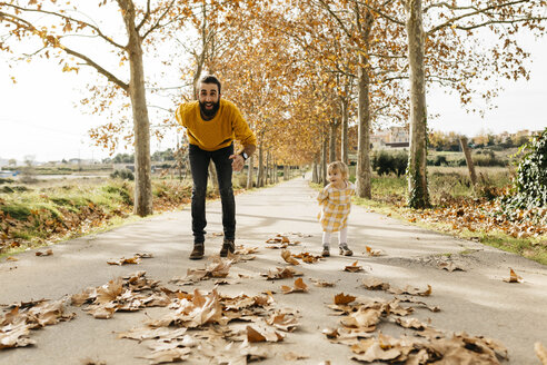 Father and daughter playing on a way in the park in autumn - JRFF02269