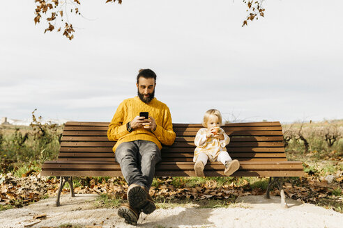 Father and daughter sitting on a bench in the park in autumn, father using smartphone, daughter eating an apple - JRFF02272