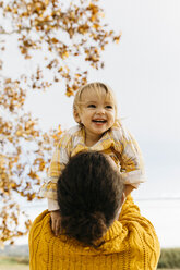 Father holding his daughter on a morning day in the park in autumn - JRFF02275