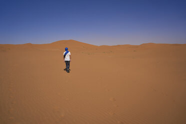 Morocco, back view of man walking on desert dune - EPF00513