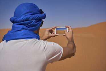 Morocco, back view of man wearing  blue tuban taking photo with smartphone in the desert - EPF00516
