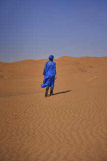 Morocco, back view of man wearing blue kaftan and turban walking on  desert dune - EPF00519