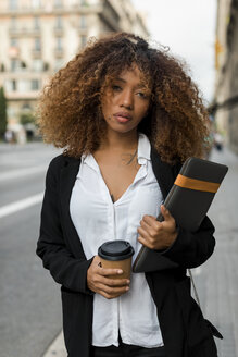 Young woman with laptop bag and coffee to go in the city, missing the taxi - MAUF02136