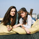 Two beautiful young women sitting outdoors - INGF11542