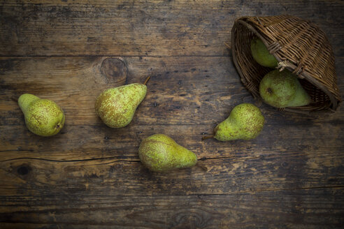 Organic pears 'Conference' and wickerbasket on dark wood - LVF07641