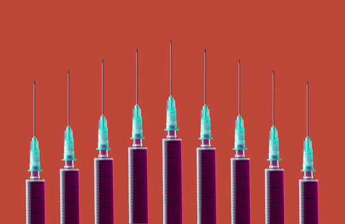 Multiple syringes organized in a pattern over orange background - DRBF00119