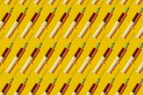 Multiple syringes organized in a pattern over yellow background - DRBF00122