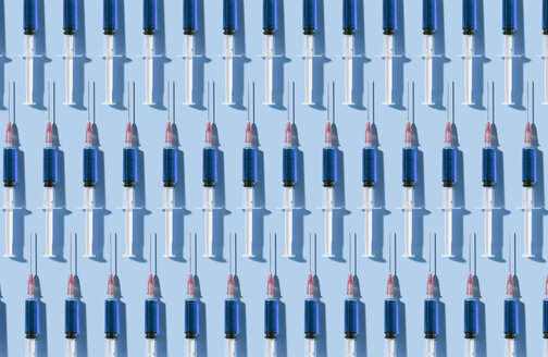 Multiple syringes organized in a pattern over blue background - DRBF00125