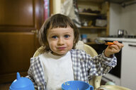 Portrait of cute toddler boy sitting in high chair in kitchen - MGIF00290