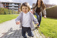Mother running behind happy toddler son on a path - MGIF00296