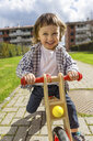 Portrait of happy toddler boy with balance bicycle on a path - MGIF00299
