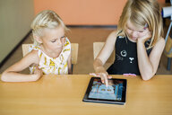 Girl watching classmate drawing on digital tablet in classroom - ASTF00019