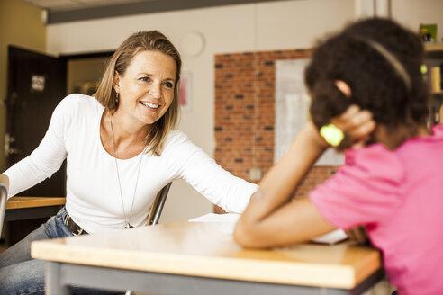 Happy mature teacher teaching girl in classroom - ASTF00046