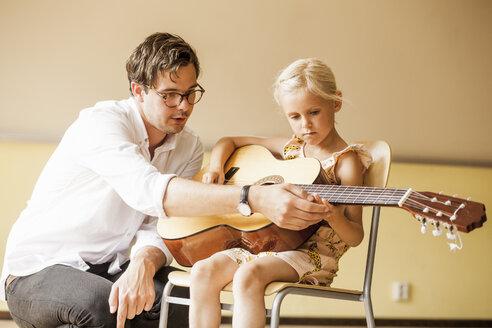 Male teacher teaching girl to play guitar - ASTF00058