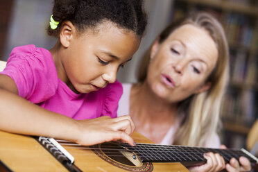 Female teacher teaching girl to play guitar - ASTF00061