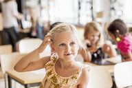 Girl scratching head while looking away in classroom - ASTF00076