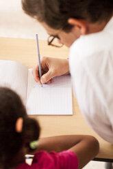 Male teacher teaching girl at desk - ASTF00079