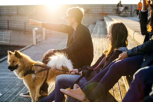 Man with dog showing something to friends while relaxing on steps outdoors - ASTF00118