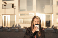 Portrait of young woman drinking coffee from disposable cup on city street - ASTF00124