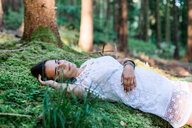 A woman lying down on grass in the forest - INGF11801