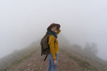Woman hiking in the fog, standing on a mountain path - AFVF02190
