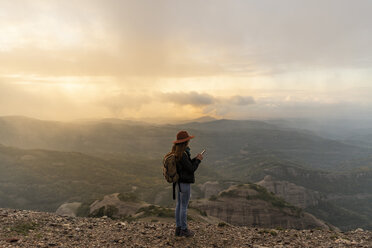 Woman with backback, standing on mountain, looking at view, using smartphone - AFVF02196