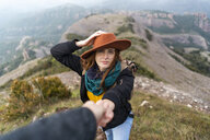 Woman with hat, standing on mountain, holding on to man's hand - AFVF02199