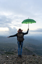 Woman standing on a mountain, looking at view, holding a green umbrella - AFVF02205