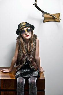 Portrait of girl wearing party clothing and oversized sunglasses sitting on sideboard - VWF00011