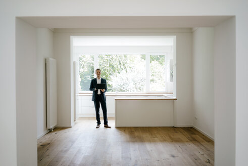 Estate agent waiting in newly refurbished home, holding laptop - KNSF05465