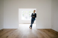 Estate agent waiting in newly refurbished home, holding laptop - KNSF05471