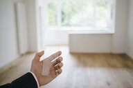 Hand holding glass touch screen in refurbished home - KNSF05474
