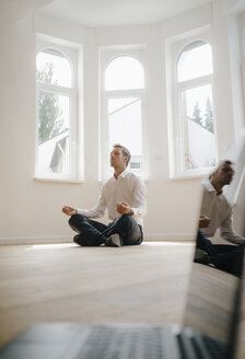 Businessman in newly refurbished home, sitting cross-legged on floor, meditating, with laptop in foreground - KNSF05483
