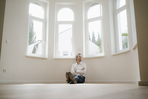 Businessman sitting on ground of his newly refurbished home, looking happy - KNSF05486