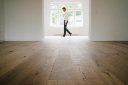 Businessman walking in empty flat - KNSF05498
