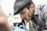 Tattoo artist tattoing hand - DAMF00026