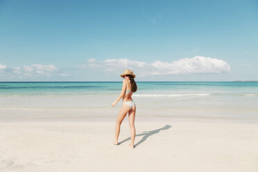 Back view of a young woman on holidays standing on the beach during a summer day. Mallorca, Balearic Islands, Spain. - LOTF00002