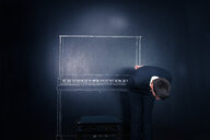A person bending over in front of a blackboard with a piano - INGF11962