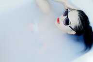 Close-up shot of a woman in the bath with sunglasses - INGF12022