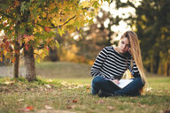 Portrait of pensive young woman with notebook sitting on meadow in a park in autumn taking notes - LOTF00006