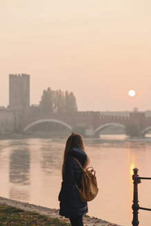 Italy, Verona, back view of woman with backpack looking at view by sunset - LOTF00012