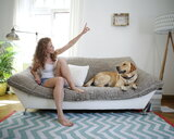 A young woman with her pet dog sitting on the sofa at home - INGF12035