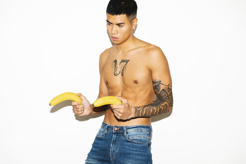 Semi-dressed young man playing with bananas like guns - MRAF00358