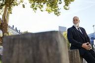 Elegant businessman leaning on a wall in the city - RHF02382
