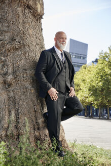 Elegant businessman leaning on tree in the city, thinking - RHF02391
